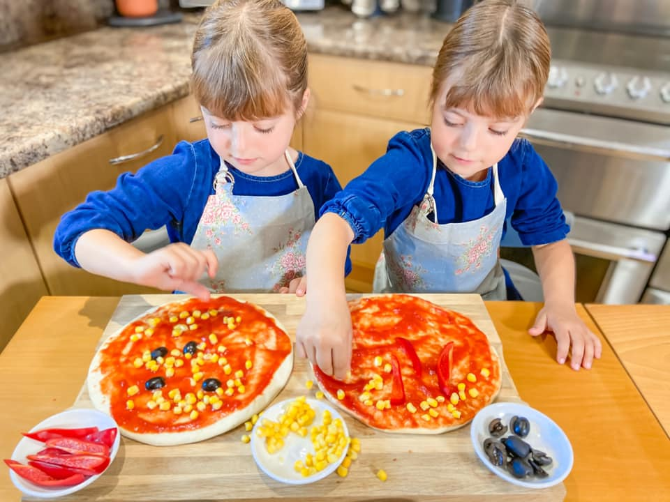 two girls sitting at a wooden table with pizza bases in front of them and they are adding cheese and sweetcorn to make Red pepper and Sweetcorn pizza
