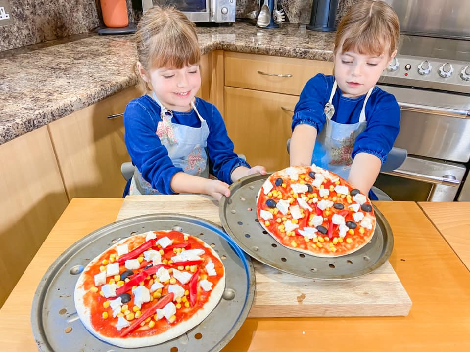 two girls sitting at a wooden table with pizza bases in front of them and they are placing their pizza on a baking tray ready to cook their Red pepper and Sweetcorn pizza