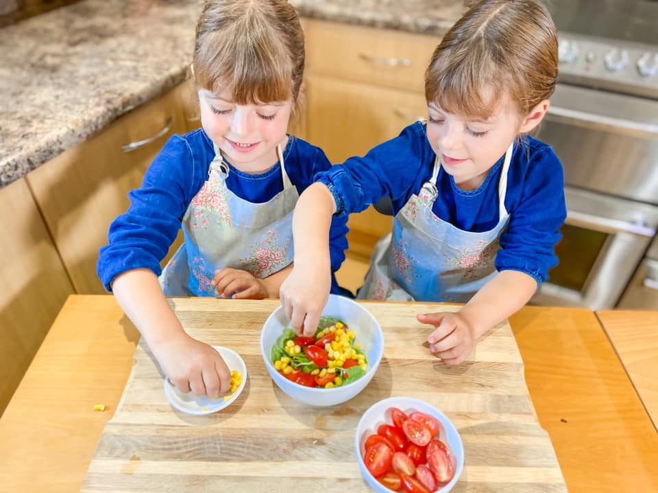 two girls sitting at a wooden table with pizza bases in front of them and they are making a rocket salad to go with their Red pepper and Sweetcorn pizza