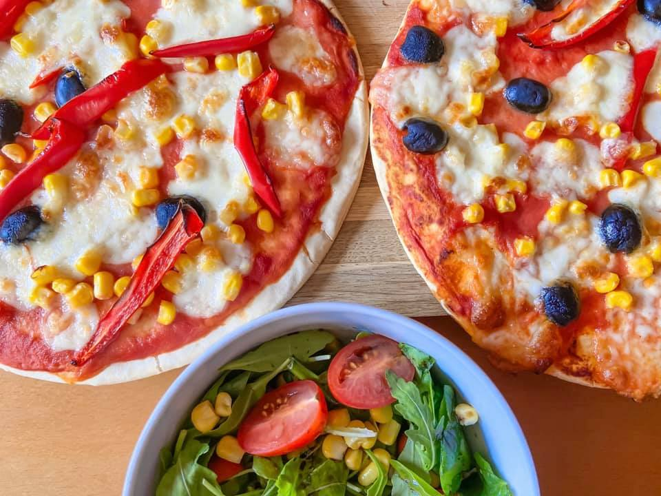 Tomato, cheese and olive pizza with a rocket salad in a white bowl