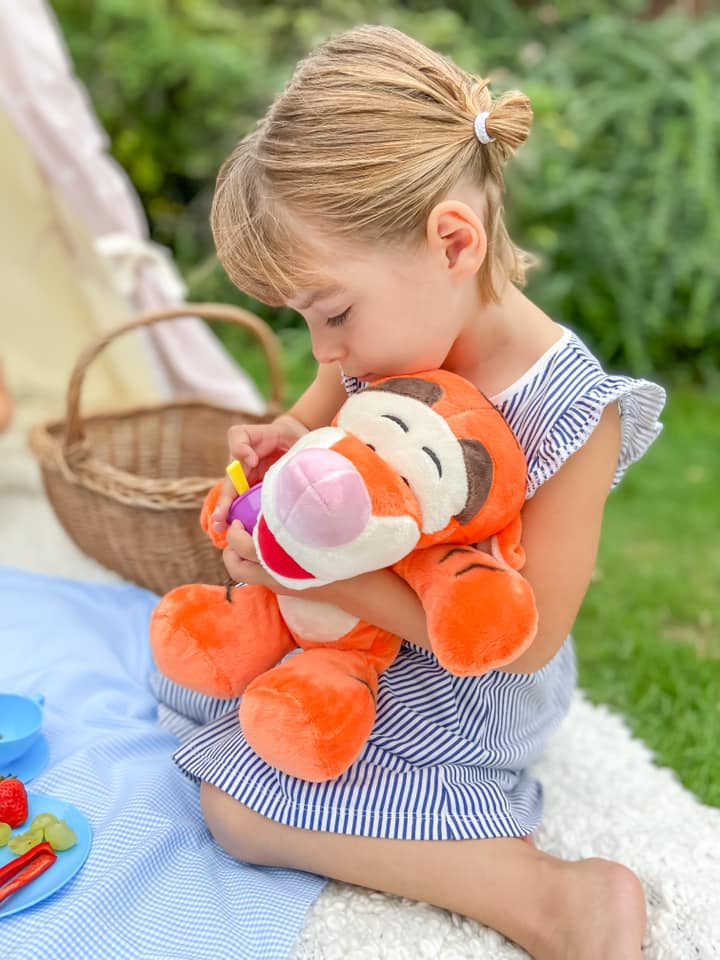little girl in a blue striped dress cuddling Tigger whilst trying to feed him some lunch