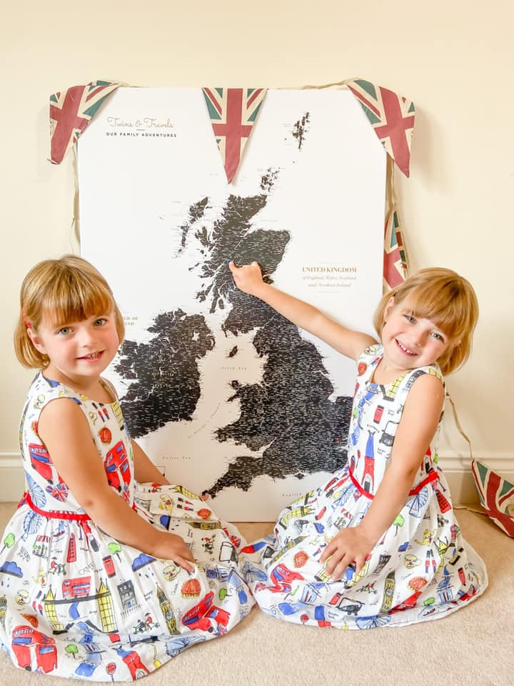 Trip Map Pin Map learning up against the wall with two girls in London dresses smiling at the camera