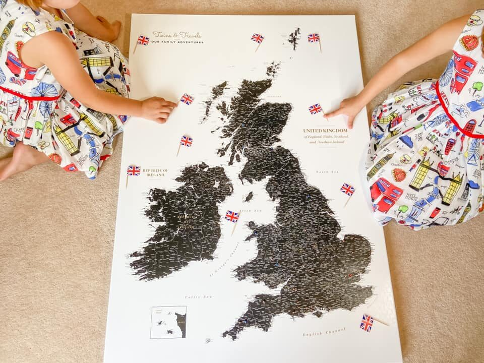 Map of the UK on the floor with two girls arms pointing at small UK flags