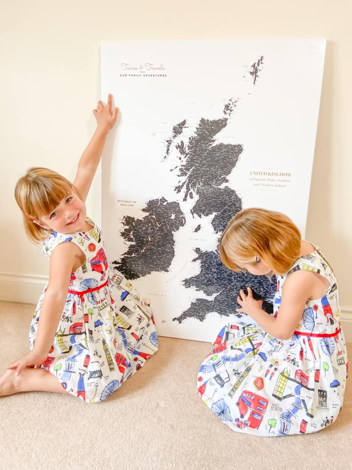 large trip map on the floor with a girl pointing to the map, and the other pinning it