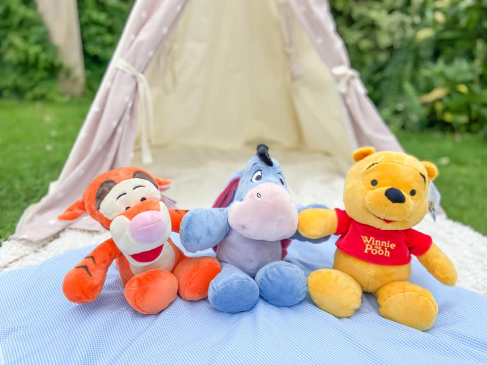 Three plush toys sitting on a white rug in front of a cream and pink teepee - Winnie the Pooh, Eeyore and Tigger