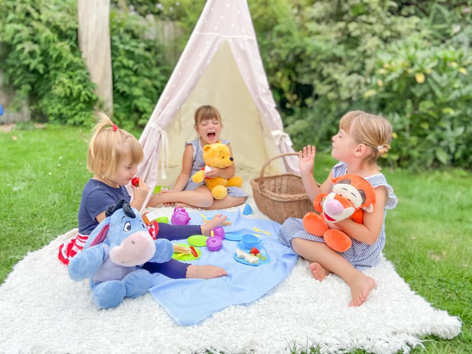 Three young girls sitting in front of a teepee in the garden on a white rug eating a picnic with Winnie the Pooh, Eeyore and Tigger