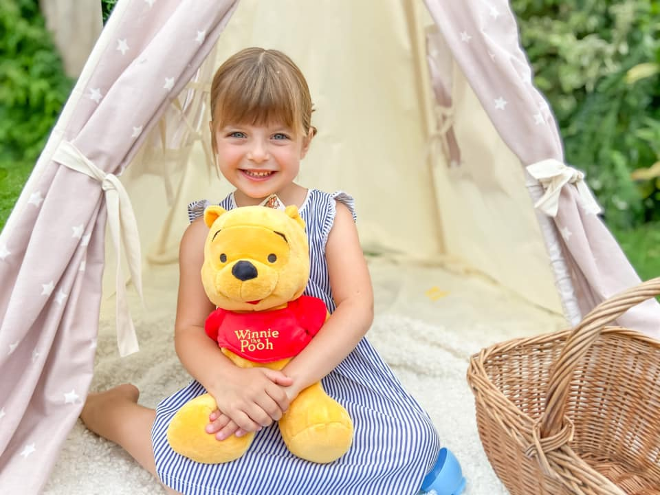 little girl in a blue striped dress cuddling Winnie the Pooh Plush toy whilst sitting on the floor