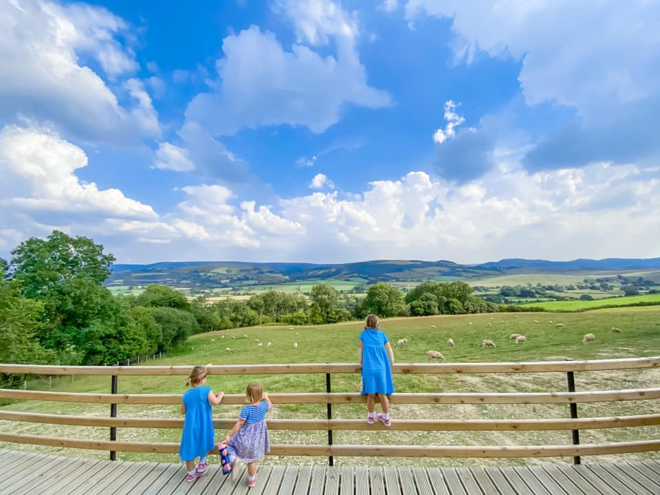 Three girls looking out over the green Welsh Hills in Wales