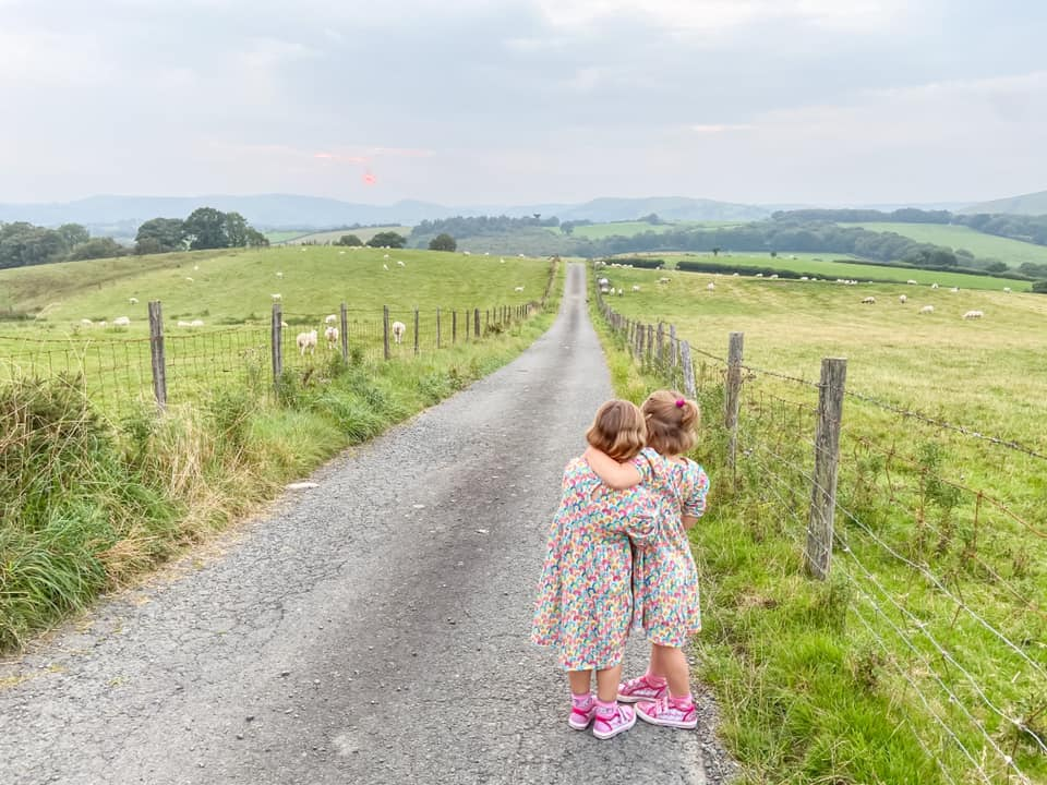 Two girls standing on a lane overlooking fields and sheep