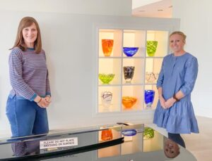 two ladies standing by a display of vases on a short break holiday