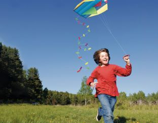 Pocket kite with a little boy running along flying it