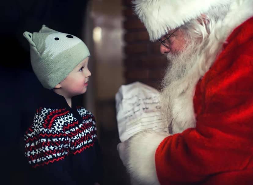 Santa bending down talking to a little boy