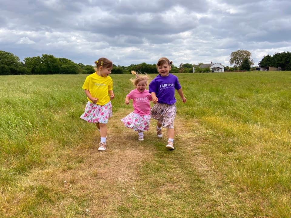 Three children running through fields