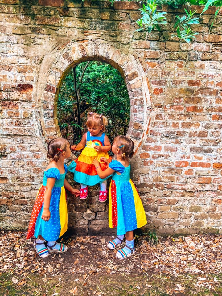 three children in bright dresses with one child sitting on a brick wall