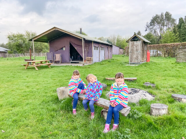 Three girls in rainbow jumpers sitting by the campfire at Featherdown Farm