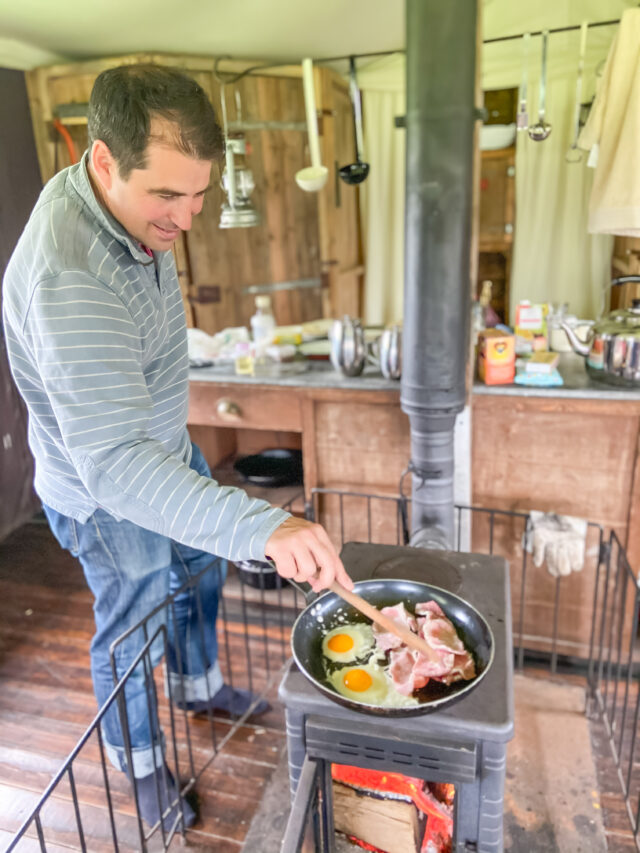 Dad cooking eggs and bacon on the log burner at Feather Down glamping