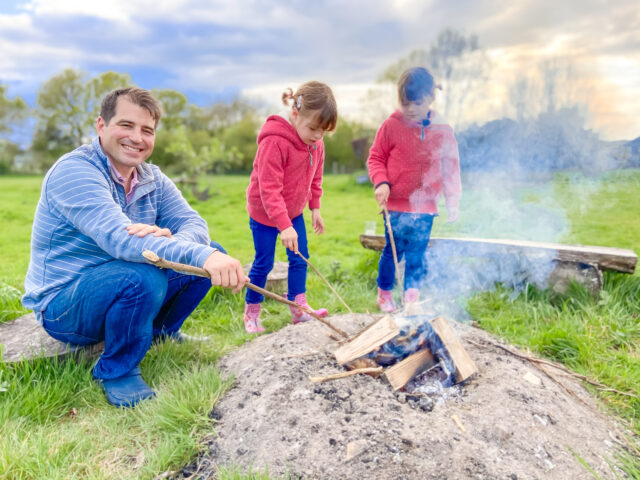 Feather Down glamping site toasting marshmallows round the campfire