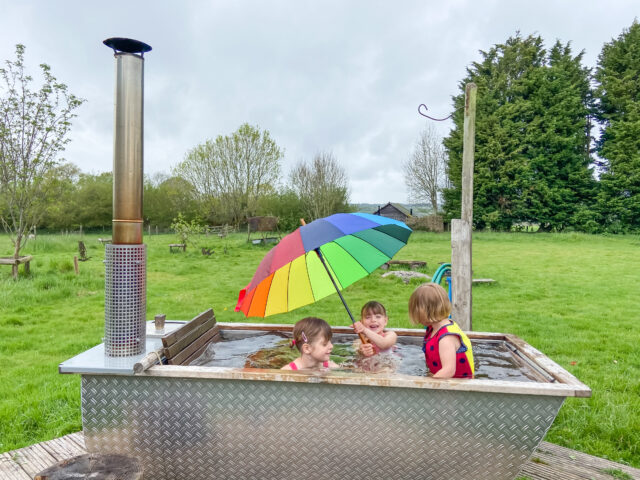 Glamping with a hot tub and grill playing in it in the rain