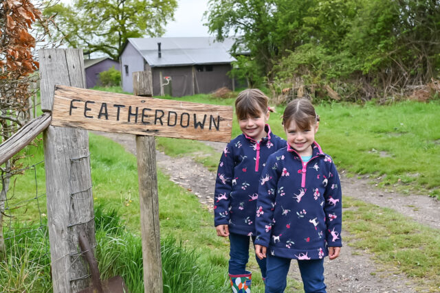 twins standing next to the Feather Down sign