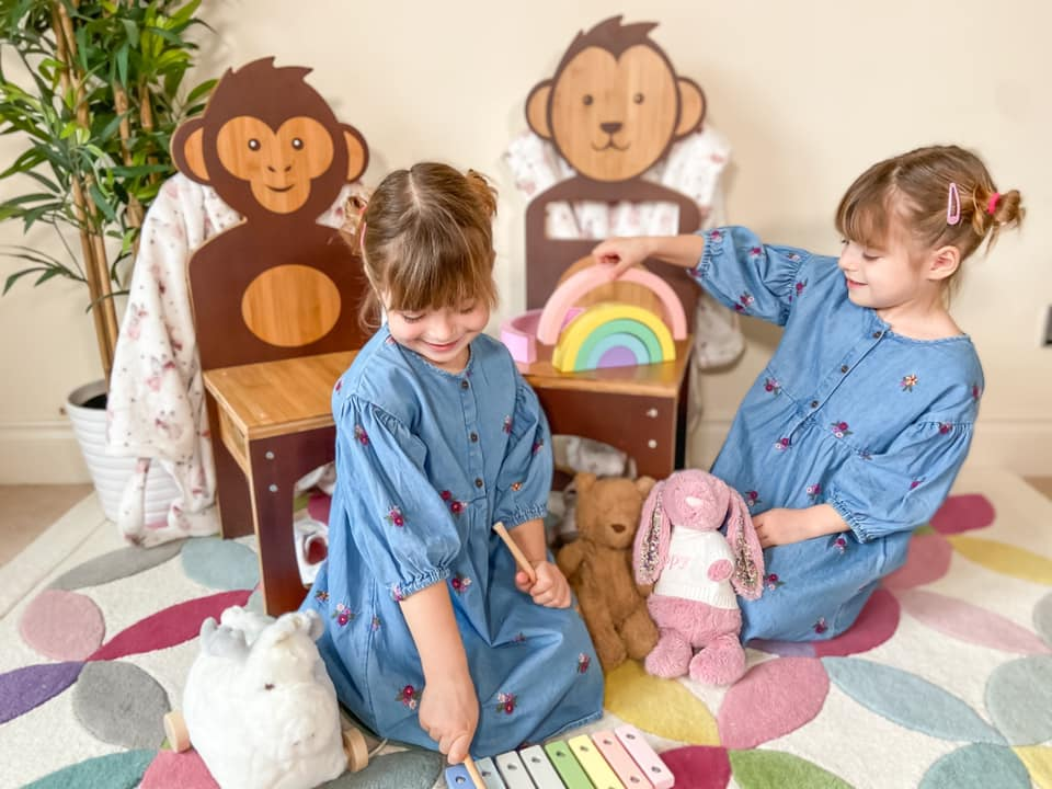 two girls sitting on the floor playing with eco friendly toys leaning on two wooden chairs in the shape of a monkey and a bear