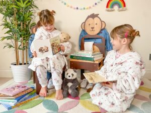 Two girls sitting on eco friendly wooden Mani Me chairs made in the shape of a bear and monkey
