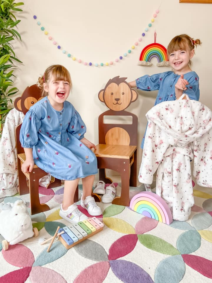 two girls laughing and leaning on their mama me wooden animal chairs