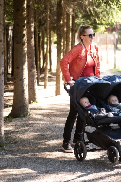 Happy Mother With Babies Stroller Walking in Zoo and Enjoying Sunny Day