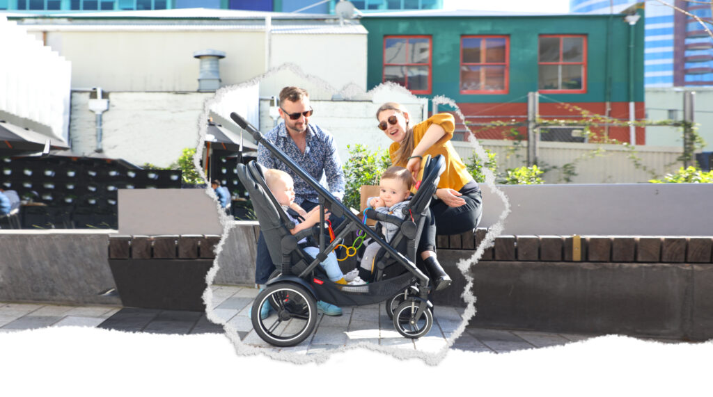 Two parents with twins looking at their children in a double buggy
