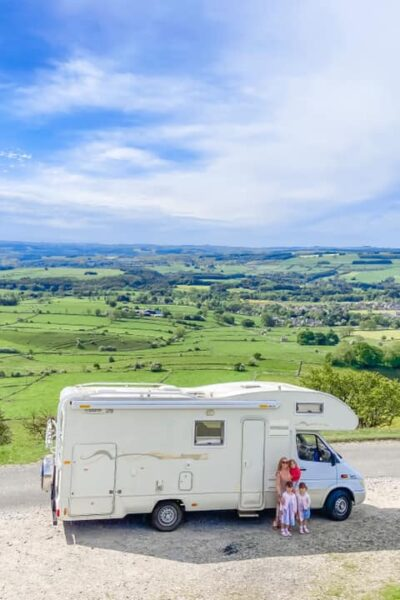 White campervan on top of a hill overlooking the Peak District