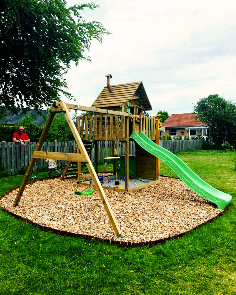 Outdoor wooden climbing frame with a green slide