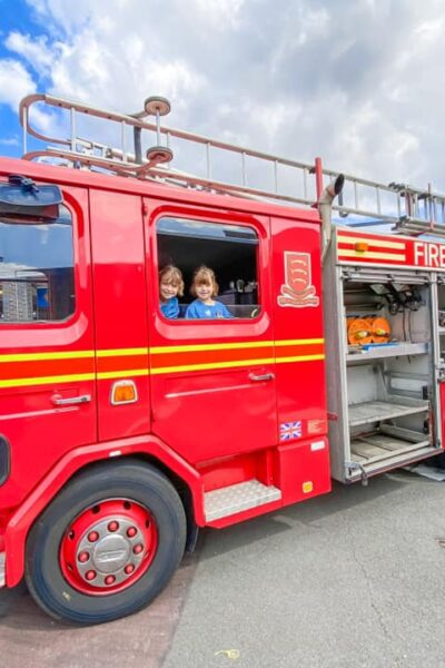 red fire engine with two girls in blue dresses looking out of the window