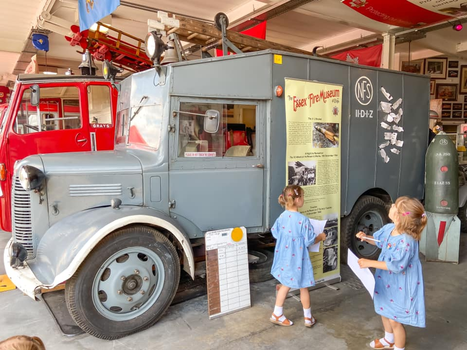 Grey fire engine with two girls in blue dresses looking at it