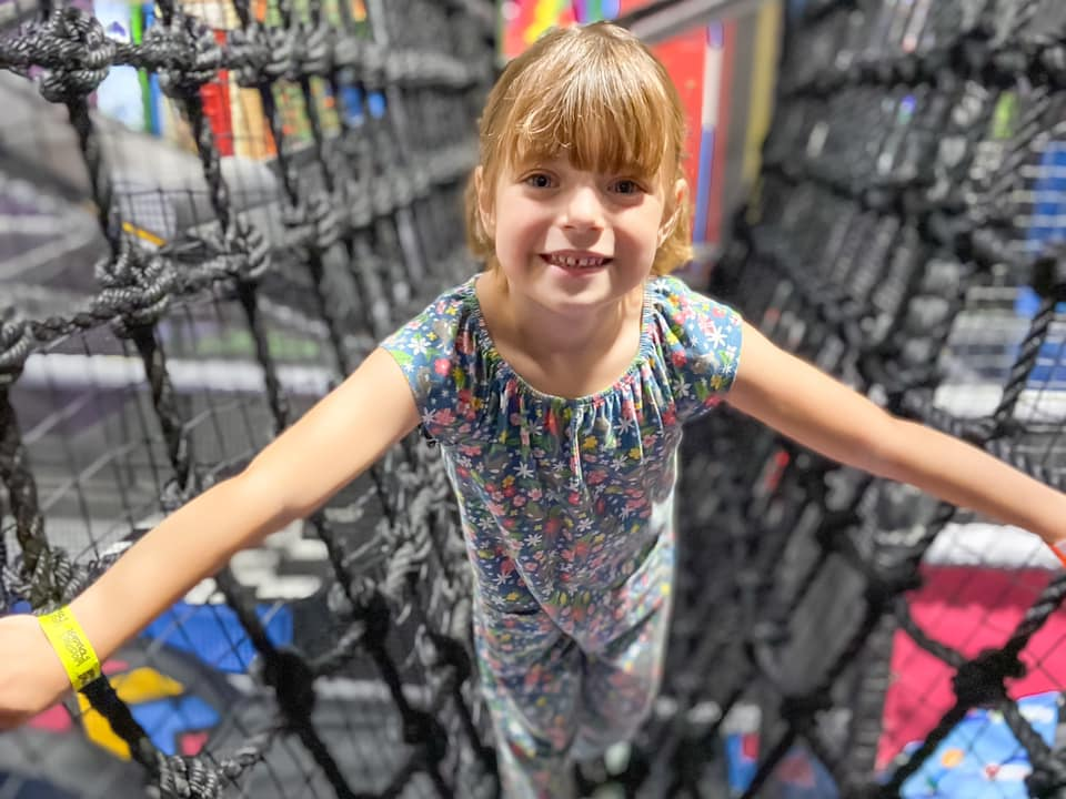girl climbing on the rope bridge at Kendricks soft play at Jump Street - days out in essex