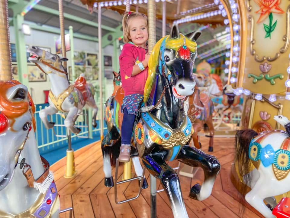 Child on a black horse on a carousel - things to do in essex