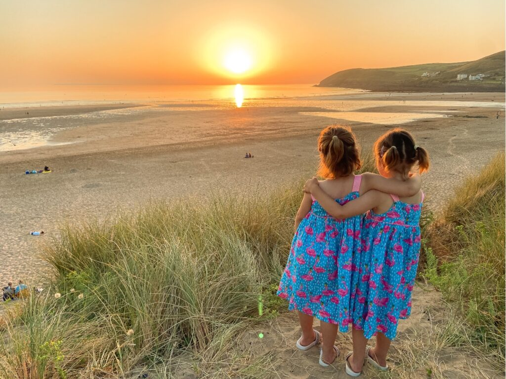 Children playing on the sand at sunset at Croyde Bay beach