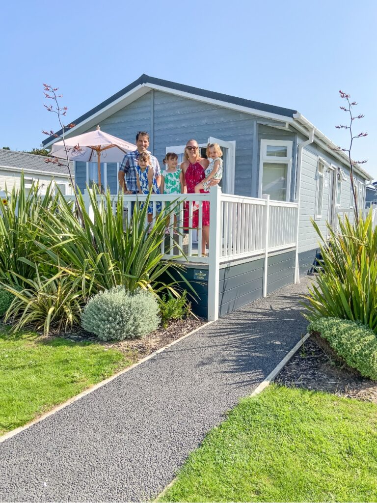 Croyde Bay Resort lodge with family standing on decking