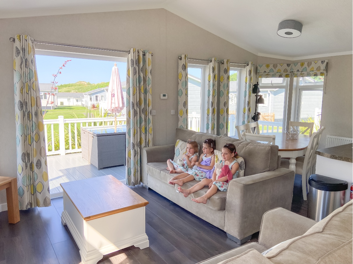 three children sitting on the sofa in a lodge at Croyde Bay Resort