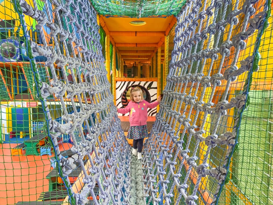 Inside Adventure soft play with child walking across a rope bridge - things to do in Essex