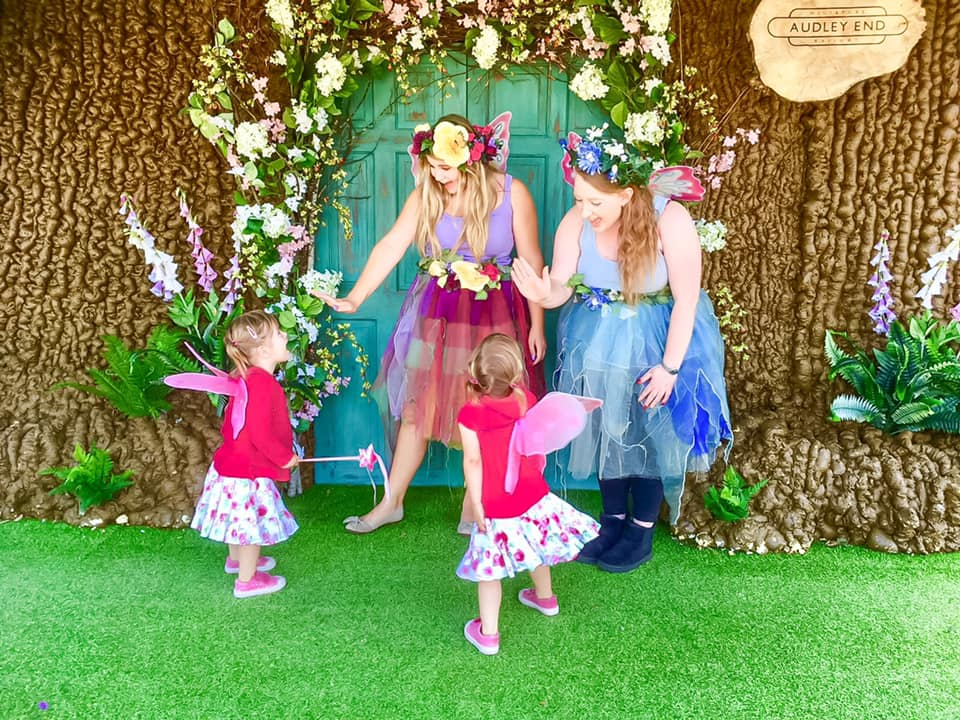 Three girls looking at a fairy house at Audley end days out in essex